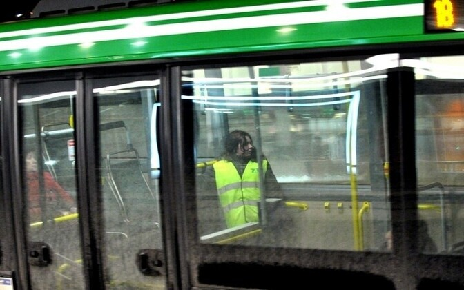 Visible through the bus window, a woman wearing a reflective vest is one of many travel escorts, who help the elderly and mothers with baby carriages get on and off of buses. The position was created by Tallinn to mitigate its high unemployment.