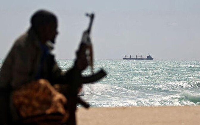 In an unrelated incident, a Somali pirate watches a hijacked Greek freighter.