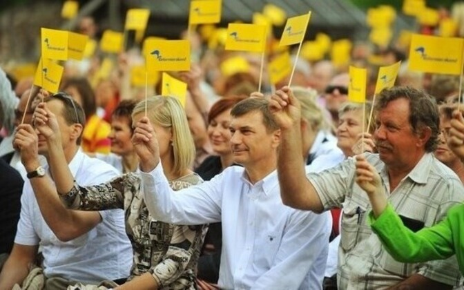 Former Prime Minister Andrus Ansip waves a Reform Party flag.