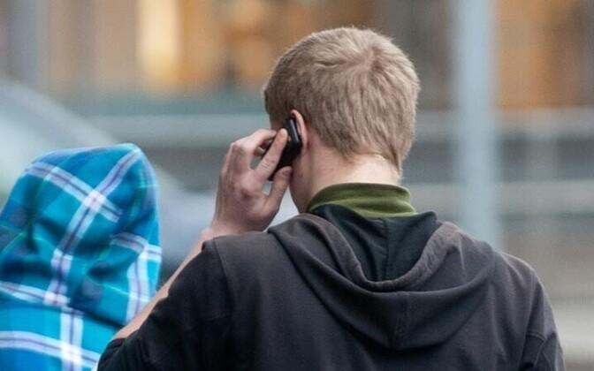 Inimene mobiiltelefoniga.