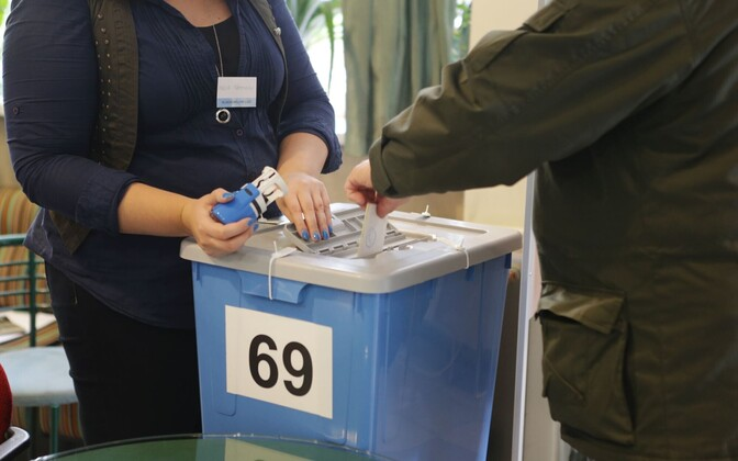 A paper ballot being stamped and placed in a secured ballot box.