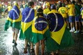 Brazil soccer fans walk in the rain after watching a broadcast of their team s loss against Germany in their 2014 World Cup semi-final match in Rio de Janeiro on Wednesday.