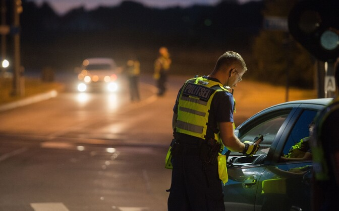 Police officer performing a breathalyser test. Image is illustrative