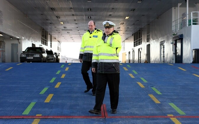 Captain Andrus Saat (hat) and first officer Aidar Leesmäe walk the auto deck of their ferry at Rohuküla harbor.
