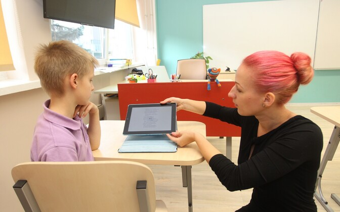 A teacher and pupil using a tablet together in the classroom.