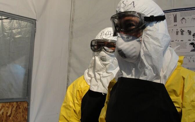 Ebola-kindlas riietuses tervishoiutöötjad.