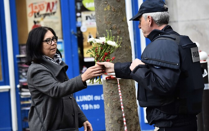 Naine palub politseinikul asetada lilled Rue de Charonne'il asuvale südmuspaigale