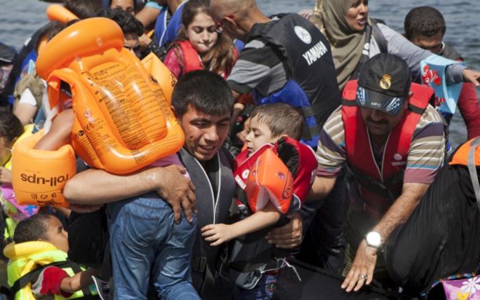 Прибытие мигрантов по морю на греческий остров.