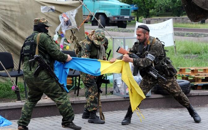 Venemaa toetatud Donetski separatistid Ukraina lippu rebimas.