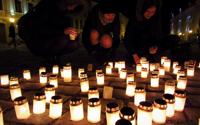 University students help light candles in memory of the victims of the 1949 deportations in Tartu's Town Hall Square, March 25, 2015.