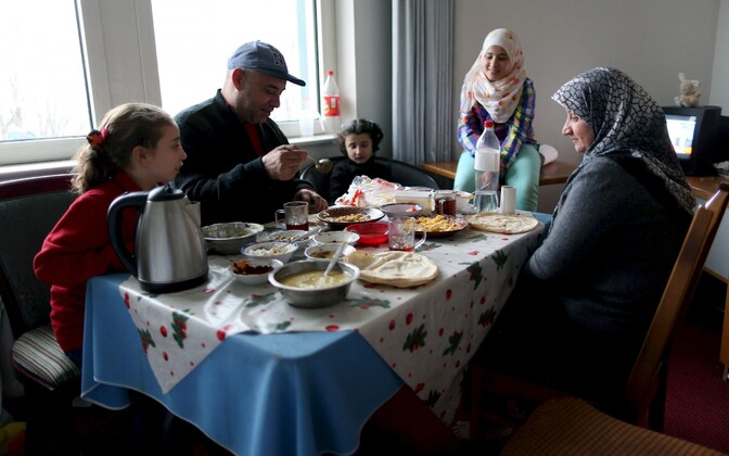 A Syrian family eats at their room at