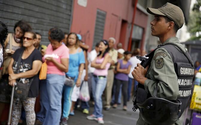 Venezuela sisevägede sõdur jahujärjekorda valvamas.