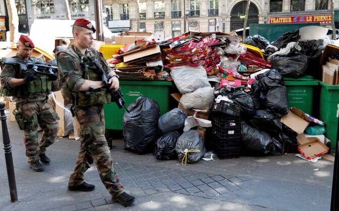 Sõdurid Pariisi tänaval prügihunnikust möödumas.