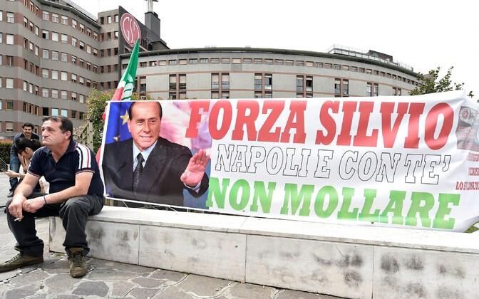 Endise peaministri toetaja Milanos San Raffaele haigla ees. Plakatil on lause: