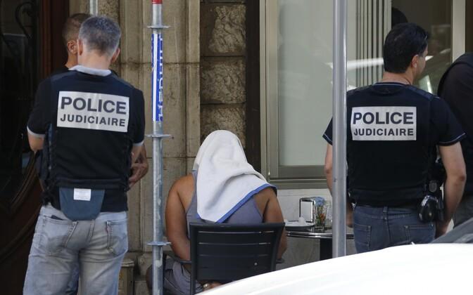 Nice'i politseinikud ümbritsemas rätikuga kaetud meest