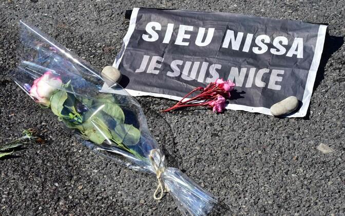 Nice'i rünnakuohvrite mälestuseks toodud lilled ja silt