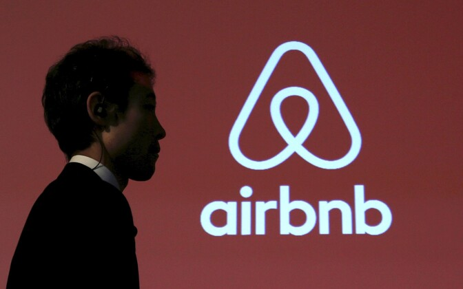 A man walks past a logo of Airbnb after a news conference in Tokyo, Japan, 26 Nov., 2015.