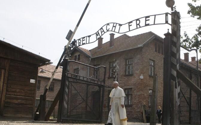 Paavst jalutamas läbi väravate, mille kohal ripub kurikuulus silt