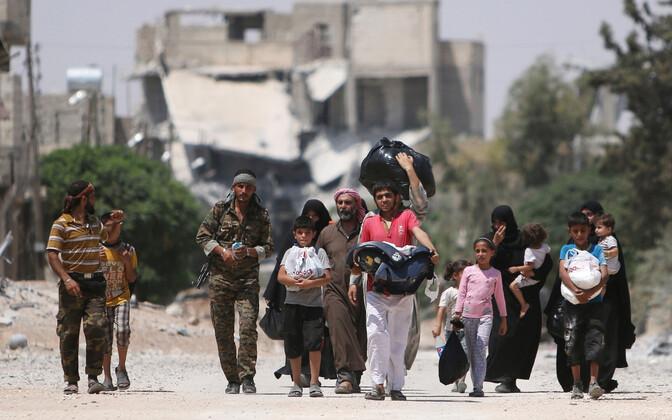 Valitsusvastased võitlejad koos sõjapõgenikega Aleppo tänaval.