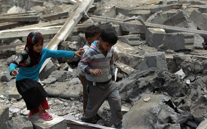 Jeemeni lapsed pärast 11. augusti araabia koalitsiooni pommirünnakuid pealinnas Sanaas varemetel kõndimas.