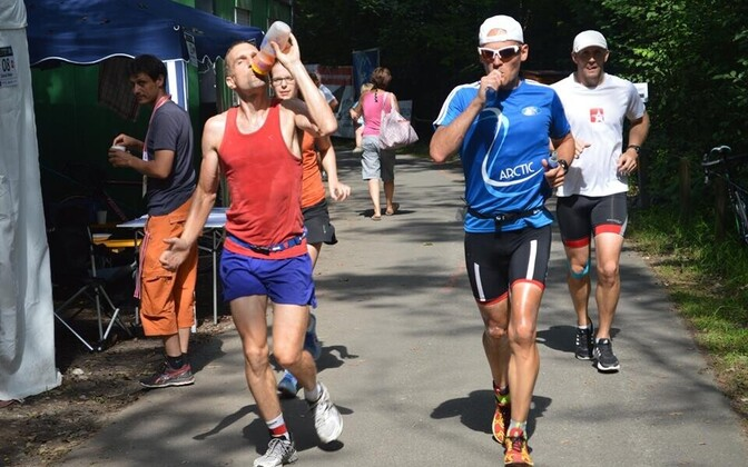 Rait Ratasepp (sinise särgiga) ja tema konkurent Richard Widmer kümnekordse triatloni viiendal päeval maratoni jooksmas.