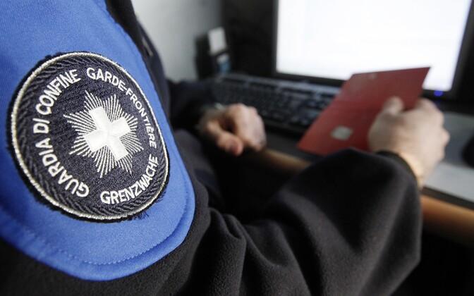 Šveitsi piirivalvur passi kontrollimas.