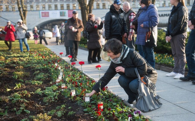 People laying flowers at the former site of the Bronze Soldier in the Tõnismäe area of Tallinn on the anniversary of the Bronze Night riots.