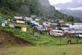 Pildil on terve küla, mille majad hävisid maavärinas. Kuna küla eelmine asupaik on praegugi liiga ohtlik ja suuresti hävinud, on elanikud paigutatud ümber kogukonnametsa, mis kuulub riigile, kuid mille eest hoolitsemine on sealsete elanike ülesanne. Elani