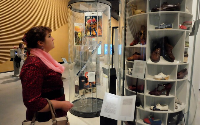 A woman checks out a display on shoe fashion throughout the decades.