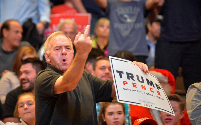 Trumpi toetaja teeb Donald Trumpi kõne ajal kampaaniaüritusel ajakirjanike suunas solvava žesti.