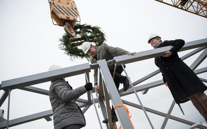 A wreath being placed on the topmost beam of the new