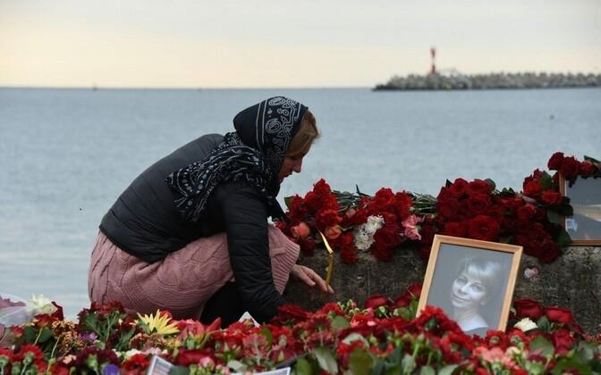 Жители Сочи приносят цветы к побережью Черного моря.