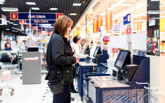 A shopper using self-checkout at a Maxima store.