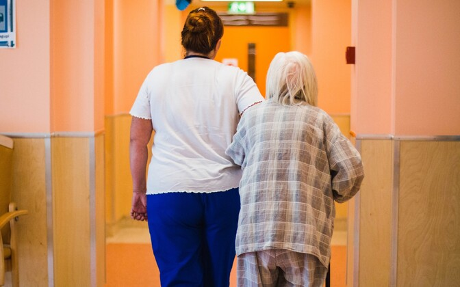 A healthcare worker walks with a patient in the hall of Pärnu Hospital's Nursing Care Centre.