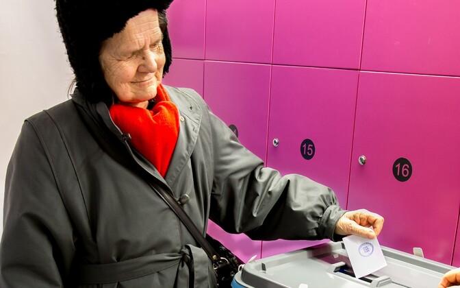 An elderly woman placing her paper ballot into a secure ballot box.