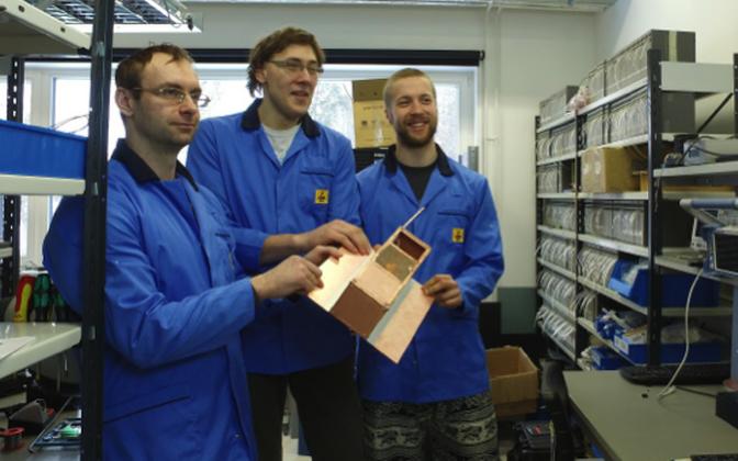 Kommunikatsiooni töögrupi liikmed poseerivad EstCube-2 elektrilise mudeliga. Vasakult: Miroslav Rolko, Laur Joost, Joosep Kivastik.