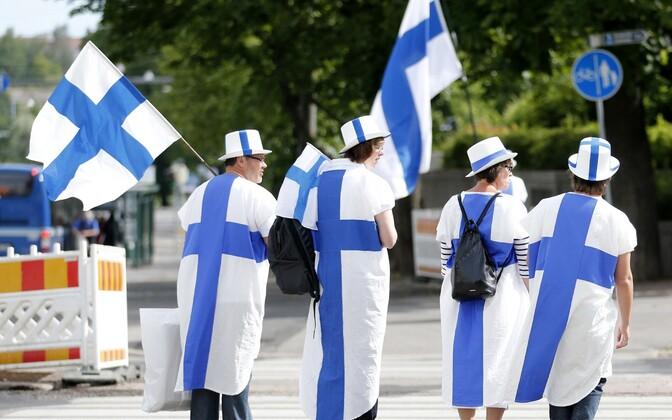 Soome lipuvärvidesse riietunud inimesed.