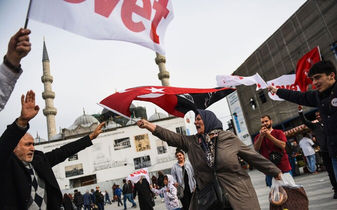 A Turkish woman supporting the no vote in the upcoming constitutional referendum waves a Turkish flag in front of Yeni Camii during a campaign rally for the yes vote in istanbul's Eminonu district. April 12, 2017.
