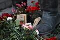 Цветы несли к памятнику на военное кладбище.