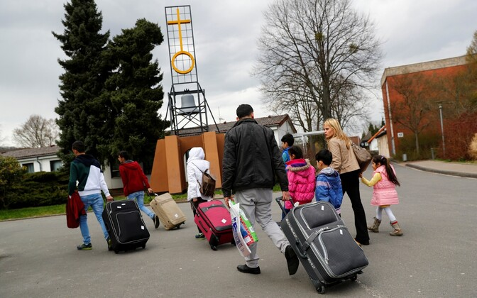 Refugees with suitcases arriving at a refugee camp in Germany. Photo is illustrative.
