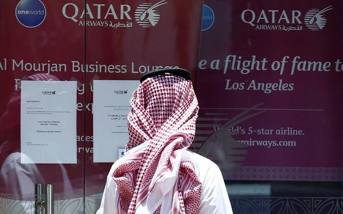 Saudi Araabia mees seismas lennufirma Qatar Airways suletud kontori ees.