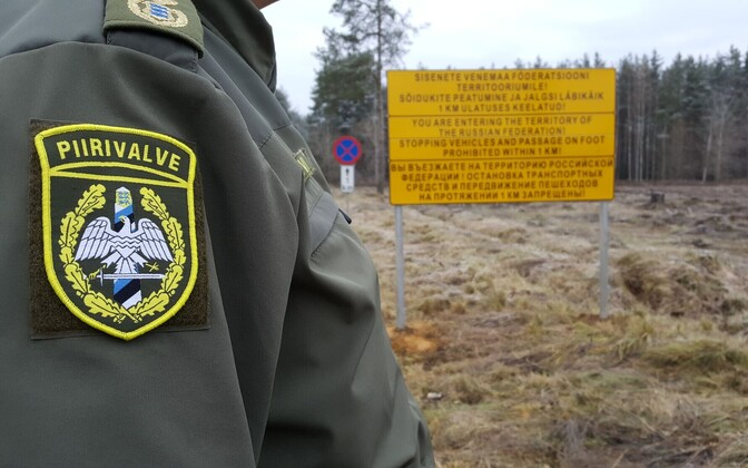 Estonian border guard with the warning sign regarding Saatse Boot visible in the background.