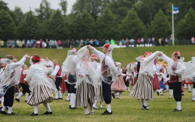 Youth folk dancers in rain ponchos at the first performance of the Youth Song and Dance Festival on Friday night. June 30, 2017.