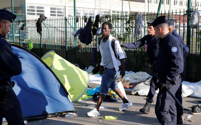 Prantsuse politseinikud pagluast eskortimas.