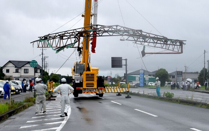 Workers remove a section of roof from the roadside, blown over by strong winds generated by Typhoon Nanmadol in the city of Kumamoto on Kyushu island on July 4, 2017. Typhoon Nanmadol has brought wind and rain to much of southern Japan.