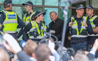 Kardinal George Pell politsei eskordi saatel kohtusse saabumas.