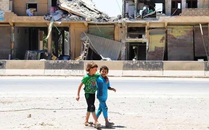Дети на улице городка в провинции Алеппо, недавно освобожденного сирийской армией.