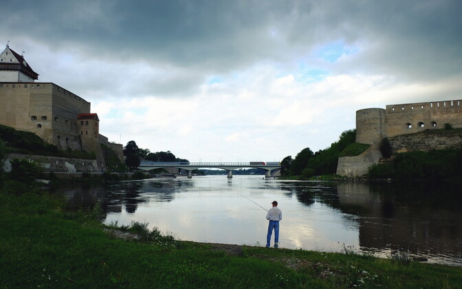 A man fishing on the Estonian bank of the Narva River where it passes between the cities of Narva and Ivangorod.