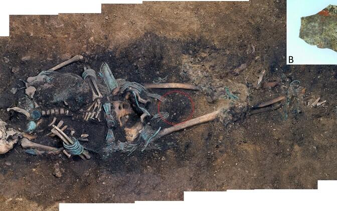 A) Kukruse kalmistu matus. Muna asukoht on tähistatud punase ringiga. B) Lähikaader osaliselt säilinud punase pigmendiga värvitud munakoore fragmendist.