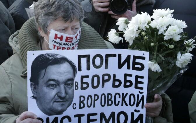 Vene opositsionäär meeleavaldusel Moskvas 2012. aastal. Plakatil Sergei Magnitski foto ja lause: